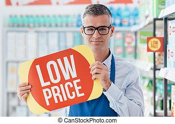 Supermarket clerk holding a sign