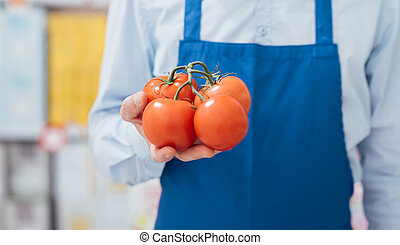 Supermarket clerk holding tomatoes