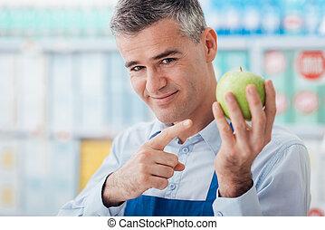 Supermarket clerk showing fresh fruit