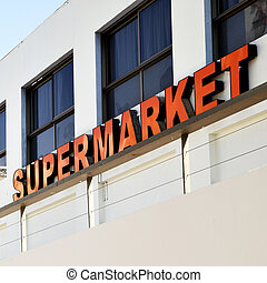 Entrance to supermarket with red signboard close-up