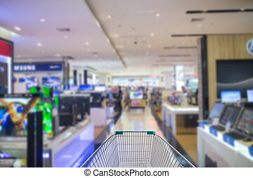 Supermarket interior, empty green shopping cart.