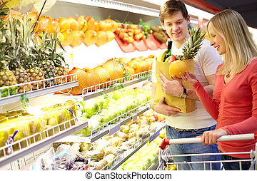 Supermarket - Portrait of couple choosing fruits in...