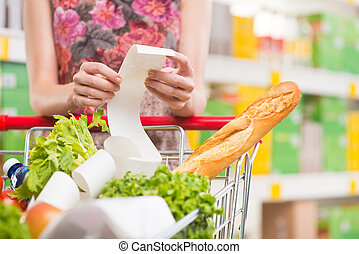 Unrecognizable woman checking a long supermarket receipt with grocery on foreground.