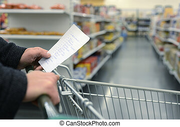 Supermarket shopping cart - Hand pushing a shopping cart...