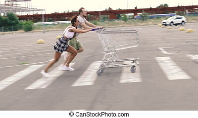 Supermarket trolley. A man and a woman are racing with supermarket carts.