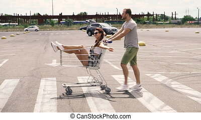Supermarket trolley. A man carries a woman to a supermarket carts.