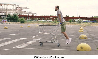 Supermarket trolley. A man rides a supermarket cart.