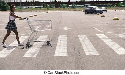 Supermarket trolley. A woman in a medical mask carries a supermarket trolley.