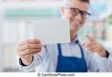 Supermarket worker holding a blank card