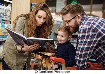 supermercato, libro, giovane famiglia, lettura