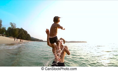 Superslowmotion shot of a father throwing his son into sea