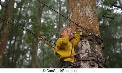 Superslowmotion shot of a little boy in a safety harness...