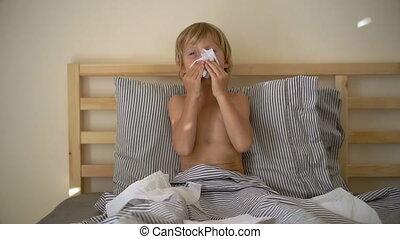 Superslowmotion shot of a sick little boy in a bed. Baby flu...