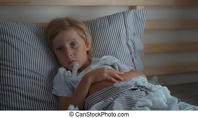 Superslowmotion shot of a sick little boy with a thermometer in a bed. Baby flu concept