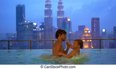 Superslowmotion shot of a young man and his little son have fun in rooftop water pool with view on skyscrapers. Travel to Asia concept