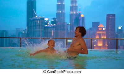 Superslowmotion shot of a young man and his little son having fun in a rooftop water pool with view on skyscrapers