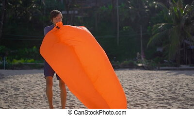 Superslowmotion shot of a young man on a tropical beach inflates an inflatable sofa. Summer vacation concept