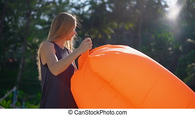Superslowmotion shot of a young woman on a tropical beach inflating an inflatable sofa. Summer vacation concept