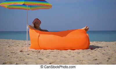 Superslowmotion shot of a young woman on a tropical beach laying down on an inflatable sofa. Summer vacation concept