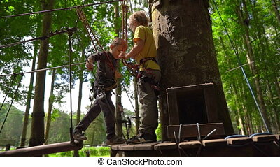 Superslowmotion shot of two little boys in a safety harness...
