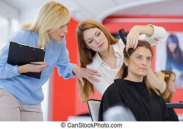 supervisor advising trainee hairdresser