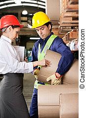 Supervisor And Foreman Checking Cardboard At Warehouse