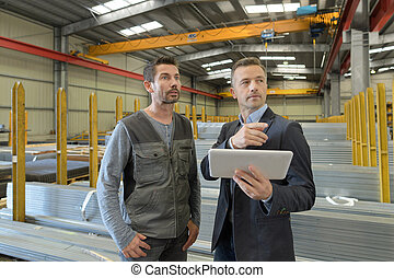 supervisor and manual worker using digital tablet in metal industry