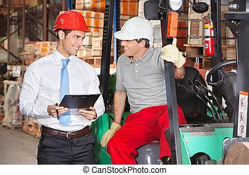 Supervisor Communicating With Forklift Driver