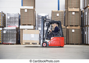 Supervisor Driving Forklift In Warehouse - Side view of male...