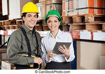 Young female supervisor instructing foreman at warehouse