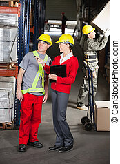 Supervisor Instructing Foreman At Warehouse