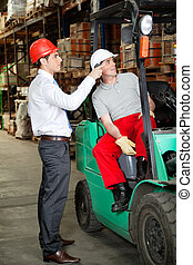 Supervisor instructing forklift driver at warehouse