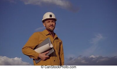 Supervisor on construction site with laptop and hardhat