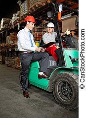 Supervisor Showing Clipboard To Forklift Driver