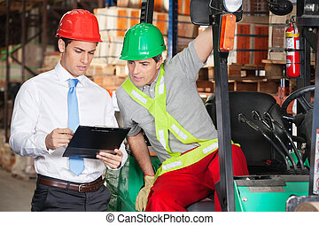 Supervisor Showing Clipboard To Forklift Driver - Young male...