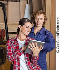 Supervisor Using Digital Tablet With Carpenter