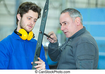 supervisor with apprentice testing hold in metal