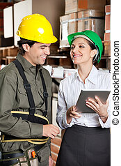 Supervisor With Digital Tablet And Foreman At Warehouse