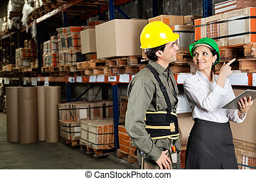 Female supervisor with foreman pointing at stock on shelves in warehouse