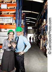 Supervisors Using Digital Tablet At Warehouse