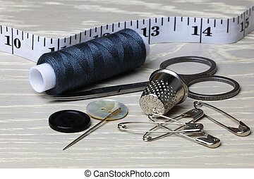 Supplies and equipment for sewing on a wood work surface cotton tape measure scissors thimble needle pins buttons