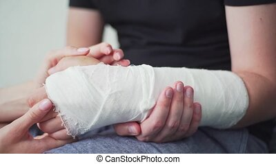 Support and care for the patient with a broken arm. The hand is in gypsum. Rehabilitation after injury, physiotherapy