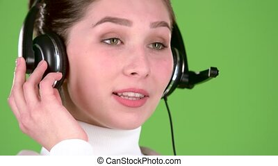 Support worker speaks to customers on the headset. Green screen. Close up. Slow motion