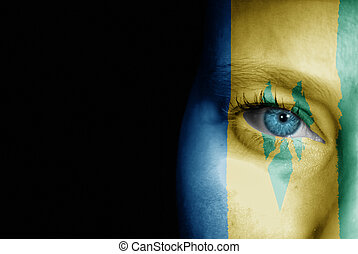 A young female with the flag of St Vincent and The Grenadines painted on her face on her way to a sporting event to show her support.