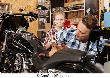 Supporting active girl handing her dad a wrench