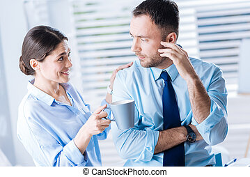 Supporting smiling woman holding a cup and looking at her gloomy colleague