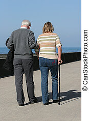 Supportive - Elderly man helping a middle aged female to...