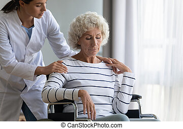 Supportive female nurse take care of disabled elderly woman