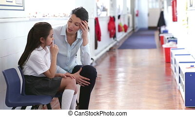 Supportive Teacher - A teacher sits in the corridor with a...