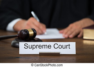 Supreme Court Nameplate With Judge Writing On Paper